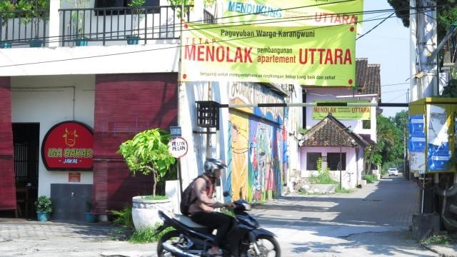 foto: moses/mahkamah Sebuah sepeda motor melintas di depan spanduk milik Paguyuban Warga Karangwuni Tolak Apartemen Uttara Jumat, 8 Mei 2015